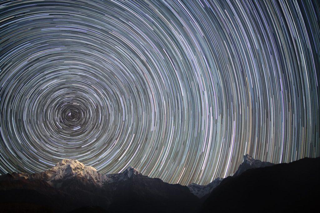 Długa ekspozycja napółnocnym niebie nadnepalskim szczytem Himalajów ukazuje pozorną ścieżkę gwiazd podczas obrotu Ziemi. Źródło: licencja: CC 0, dostępny winternecie: commons.wikimedia.org.
